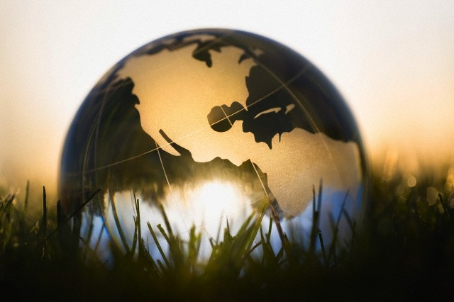 Globe in grass against sunrise